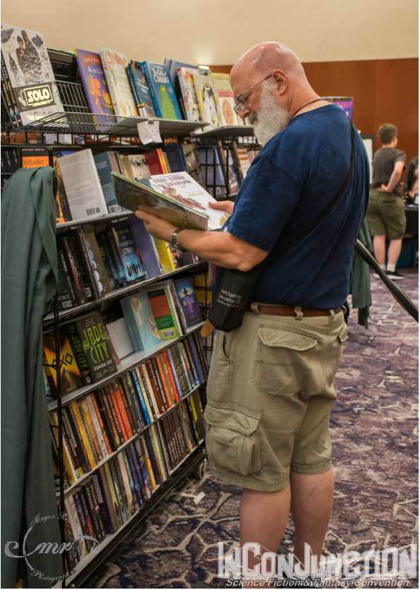 A man reading a book in front of a large rack of books for sale