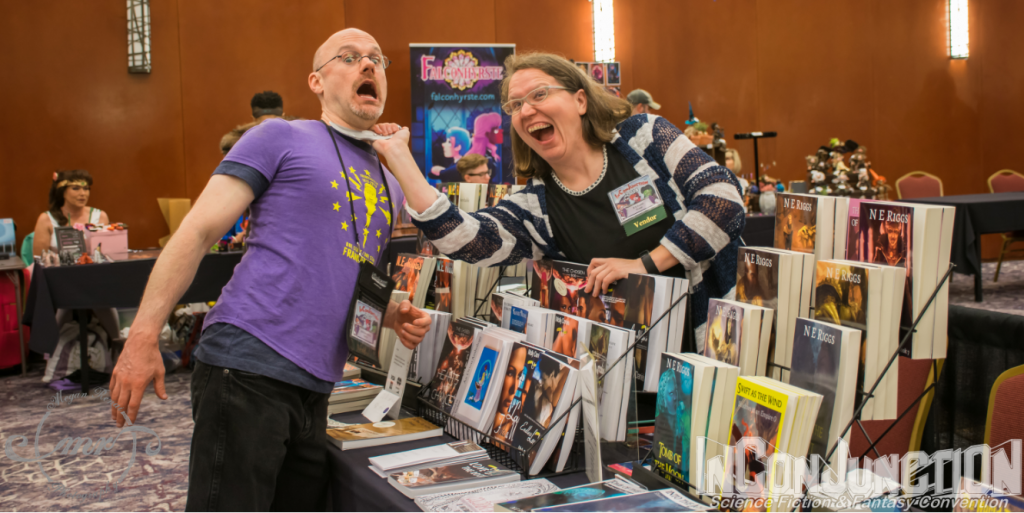 A pair of authors mock fight across a display of books on a table