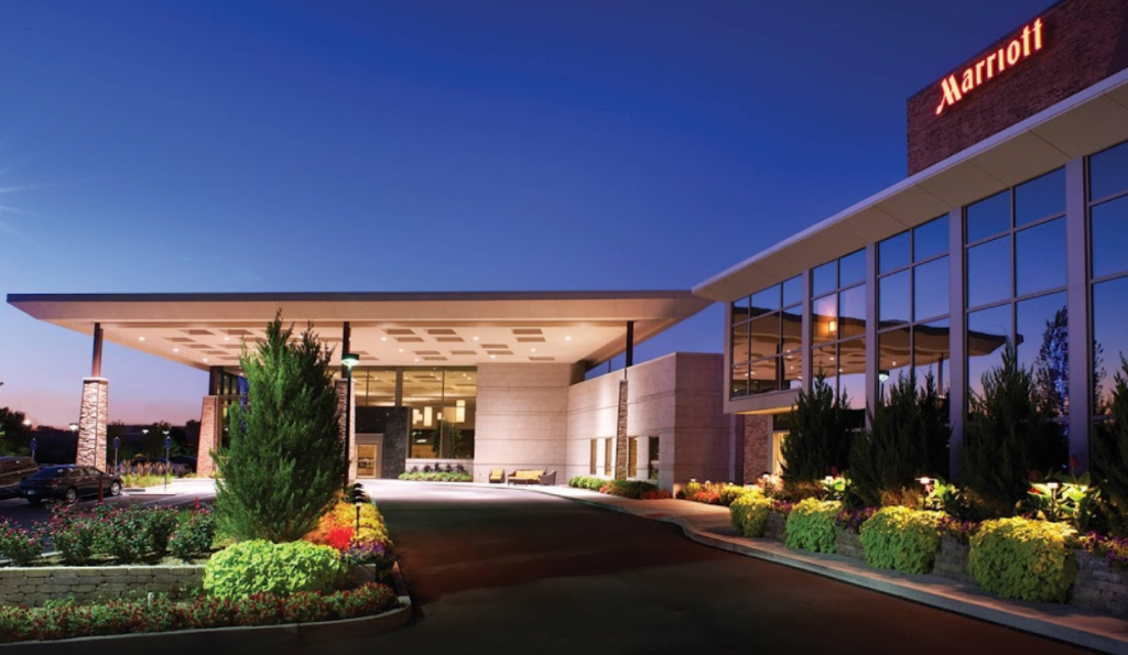 Hotel exterior on a clear night at twilight, featuring a covered entrance and landscaping beds.