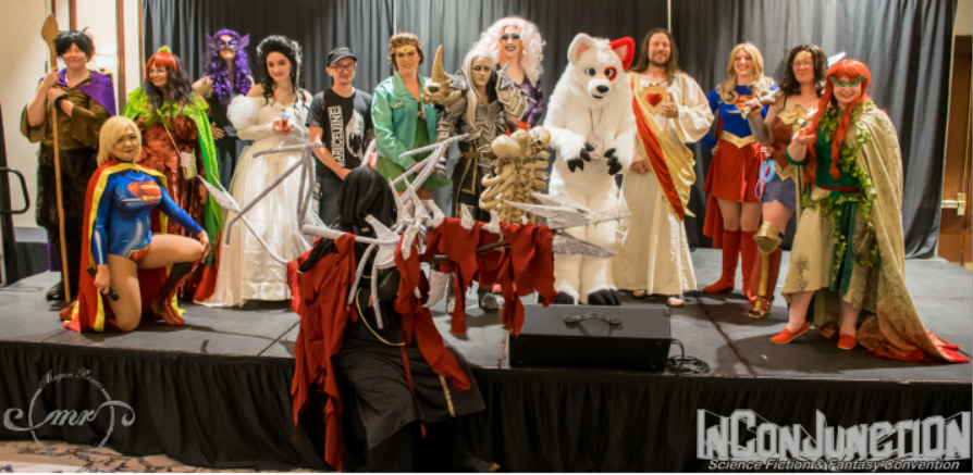 A group of people dressed as fantasy characters pose on a stage