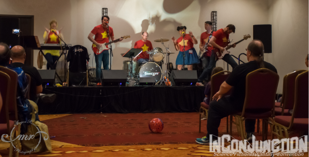 A rock band dressed in red shirts with yellow stars perform on a stage